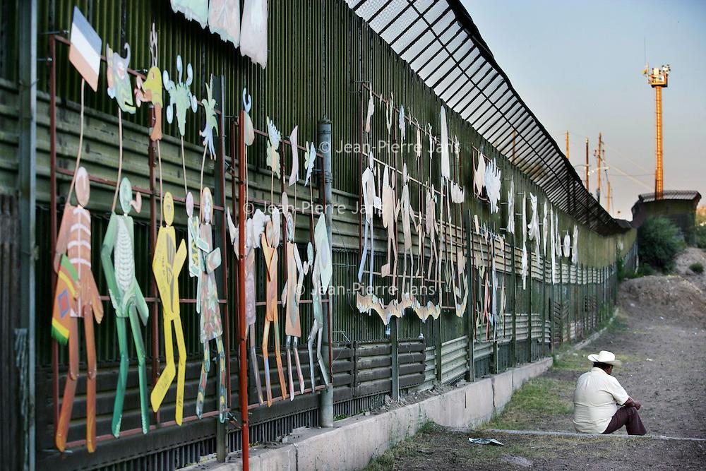 Mexico.Nogales. juli 2005.<br /> Een bewoner van het Merxicaanse grensstadje Nogales zit aan de Mexicaanse gedeelte van Nogales naast de ijzeren muur, die het stadje in tweeen deelt. Aan de andere kant ligt het veel welvarender Amerikaanse gedeelte van Nogales.<br /> Via Nogales proberen vele illegalen de Verenigde Staten binnen te komen, vandaar dat de Amerikanen deze muur hebben opgetrokken, die letterlijk de stad in tweeen verdeelt.<br /> De Amerikaanse grenspolite patrouillert voortdurend langs deze grens op zoek naar vooral Mexicaanse illegalen, die de Verenigde Staten zijn binnengedrongen.Grens.Muur.Grensproblematiek.Versiering .Hoed.Mexicaan.Illegale vluchtelingen.Uitkijkpost.Grenzen dicht.<br /> illegal<br /> Archives 2005. Chase by police on illegal Mexicans who cross the border in Arizona. The border with observation posts.