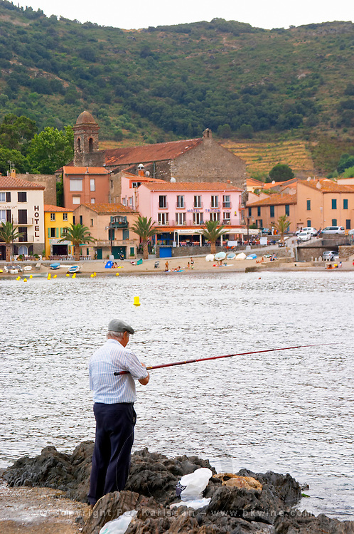 Man fishing with a fishing rod. The beach in the village. Collioure. Roussillon. France. Europe.