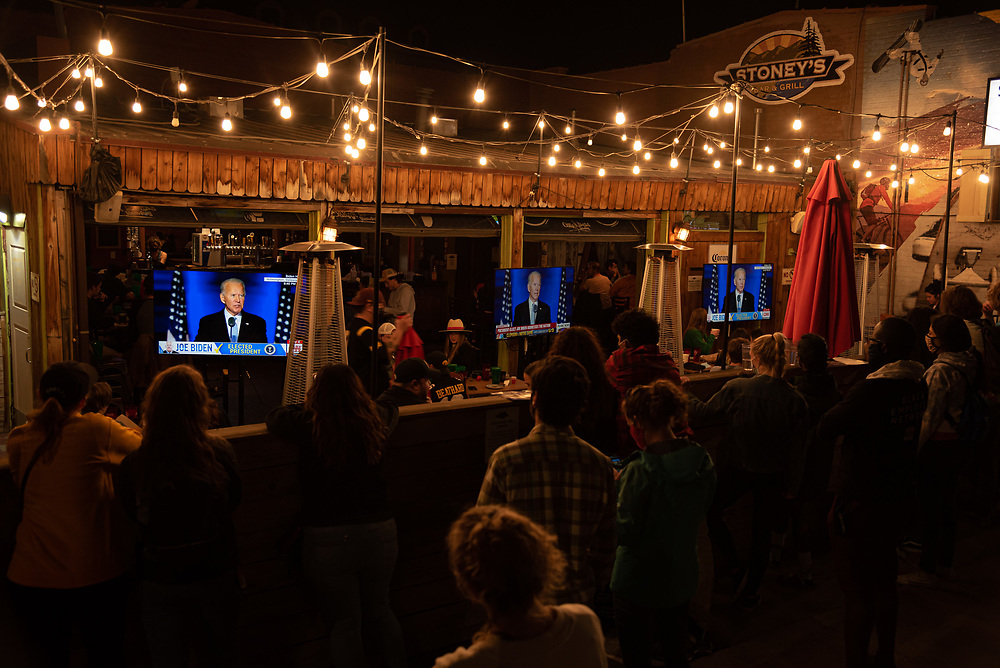People watch the president-elect Joe Biden's victory speech standing outside Stoney's bar and grill  in Denver after victory of Joe Biden in the presidential election in United States on 11/07/2020. Photograph by Akash Pamarthy.