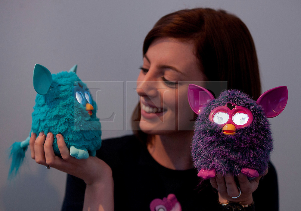 © Licensed to London News Pictures. 19/07/2012. LONDON, UK. Kely Philp, a member of staff from toy producer Hasbro looks at the latest incarnation of the Furby animatronic doll during the company's 'Christmas in July' toy launch in London today (19/07/12). First introduced in 1998, the newest version of the Furby now works with Apple iPhone, iPad and iPod touch and is set to hit the shops for Christmas 2012 priced at GB£59.99. Photo credit: Matt Cetti-Roberts/LNP