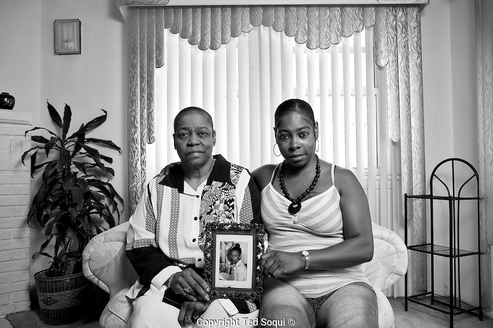 Betty, mother, Kenneitha, younger sister of Mary Lowe. They are holding the only picture they have of Mary. Photo was taken at Betty Lowe's home.