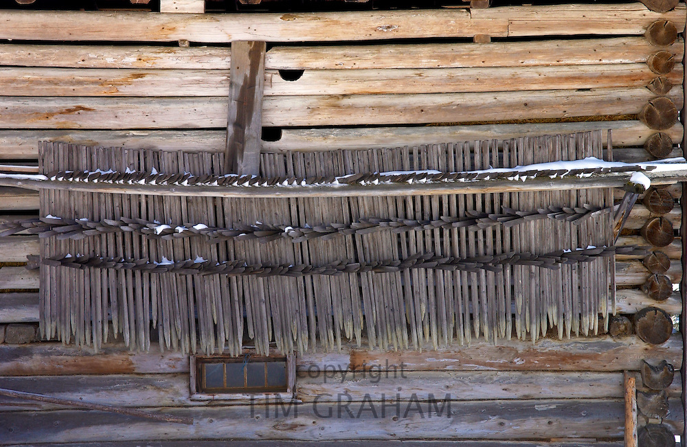Klosters - Amongst the Silvretta group of the Swiss Alps.Tools for summer hay harvest stored on the side of traditional wooden barn.