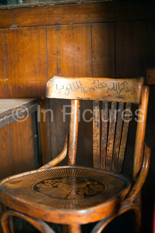 """A wooden chair engraved with a verse from the Koran that states """"With the remembrance of God's name, one's heart feels safe"""" in the Gold Star cafe, Cairo, Egypt"""