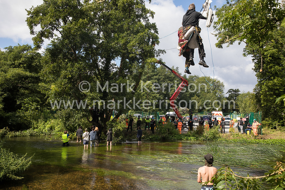 Denham, UK. 24 July, 2020. Environmental activists from HS2 Rebellion, including Swan (l) and Larch (r) on a line above the shallow river Colne, try to protect an ancient alder tree from destruction in connection with works for the HS2 high-speed rail link in Denham Country Park. A large policing operation involving the Metropolitan Police, Thames Valley Police, City of London Police and Hampshire Police as well as the National Eviction Team was put in place to enable HS2 to remove the tree.
