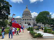 6/28/2020 Jackson MS. <br />  Pictured outside the Mississippi State Capitol is a small group of Confederate Flag supporters and Black lives Matter advocates.  Confederate symbol on the morning of the historic legislator vote. The Mississippi State legislators gathered at the State Capitol Sunday for a historic vote on HB1796. The MS House of Representatives  passed the Bill91-23 and the MS Senate voted 31-14 in favor of changing the flag. The Bill would allow for the redesign of the Mississippi State Flag, the current flag has the Confederate symbol on it. Mississippi is the last State in the Nation to still have the racist Confederate symbol on its state flag. Black Lives Matter advocates celebrated the historic vote outside the Capitol. The Mississippi House of Representatives passed the Bill and so did the Mississippi Senate, Governor Tate Reeves said he would sign it if it passed. Photo © Suzi Altman