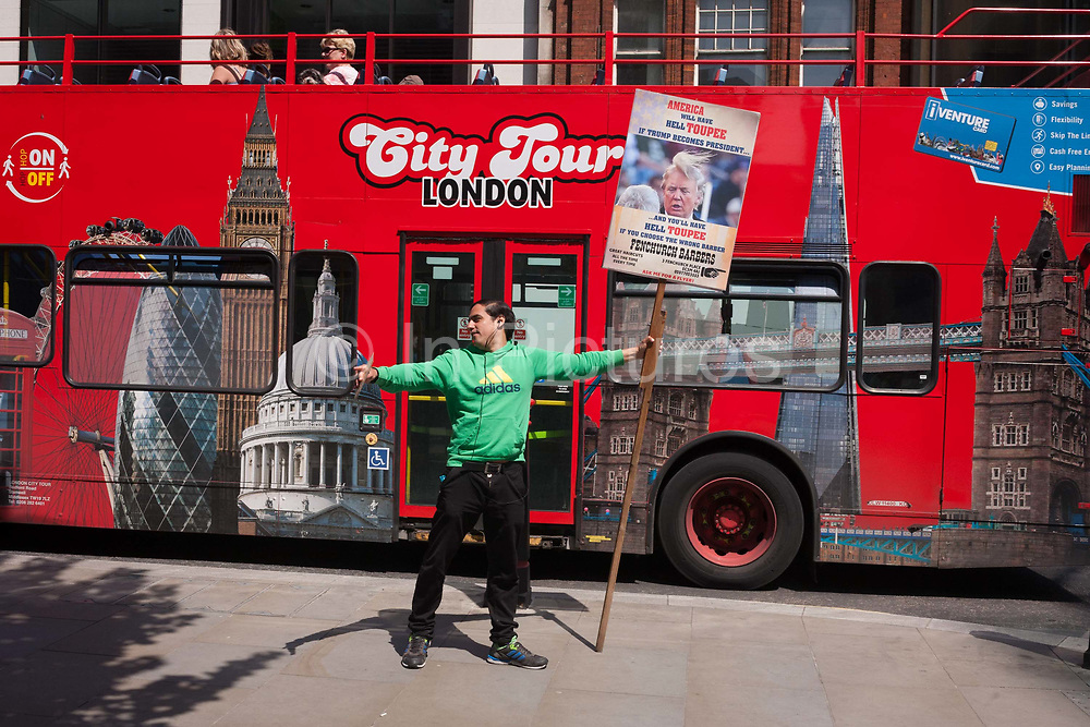 A man from a local barber shop advertises his business with a placard featuring a satire on Donald Trumps toupee wig in Fenchurch Street in the City of London, on 9th June 2016, in London, United Kingdom. Just as a tour bus with London landmarks passes-by on this busy street in the financial heart of the capital, the man stretches out his arms to attract pedestrians into his shop for a lunchtime haircut.