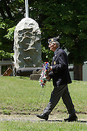 Hamptonburgh, N.Y.  -  A veteran and American Legion member carries a wreath through Hamptonburgh Cemetery during Memorial Day ceremonies at Hamptonburgh Cemetery on May 25, 2009. This was the 142nd year flowers have been placed at veterans' graves at the cemetery.