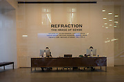 Receptionists work behind computer screen in a central Lndon art gallery.