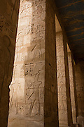 Hieroglyph columns at the ancient Egyptian site of Medinet Habu (1194-1163BC), the Mortuary Temple of Ramesses III in Luxor, Nile Valley, Egypt. Medinet Habu is an important New Kingdom period structure in the West Bank of Luxor in Egypt. Aside from its size and architectural and artistic importance, the temple is probably best known as the source of inscribed reliefs depicting the advent and defeat of the Sea Peoples during the reign of Ramesses III.
