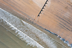 Portobello, Scotland, UK. 3 April 2021. Easter weekend crowds descend on Portobello beach and promenade to make the most of newly relaxed  Covid-19 lockdown travel restrictions and warm sunshine with uninterrupted blue skies. Pic; Aerial drone view of wave patterns at a groyne on Portobello beach.   Iain Masterton/Alamy Live News