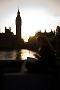 As the sun sets across the river, we see a young lady reading a book in a quiet moment on the Thames, opposite Big Ben and the Houses of Parliament. Delicately, the girl holds a cigarette in her right-hand's fingers and sits cross-legged on the embankment wall. The tall clock tower that contains the Big Ben bell rises in the evening sky, weeks before the nation's general election.