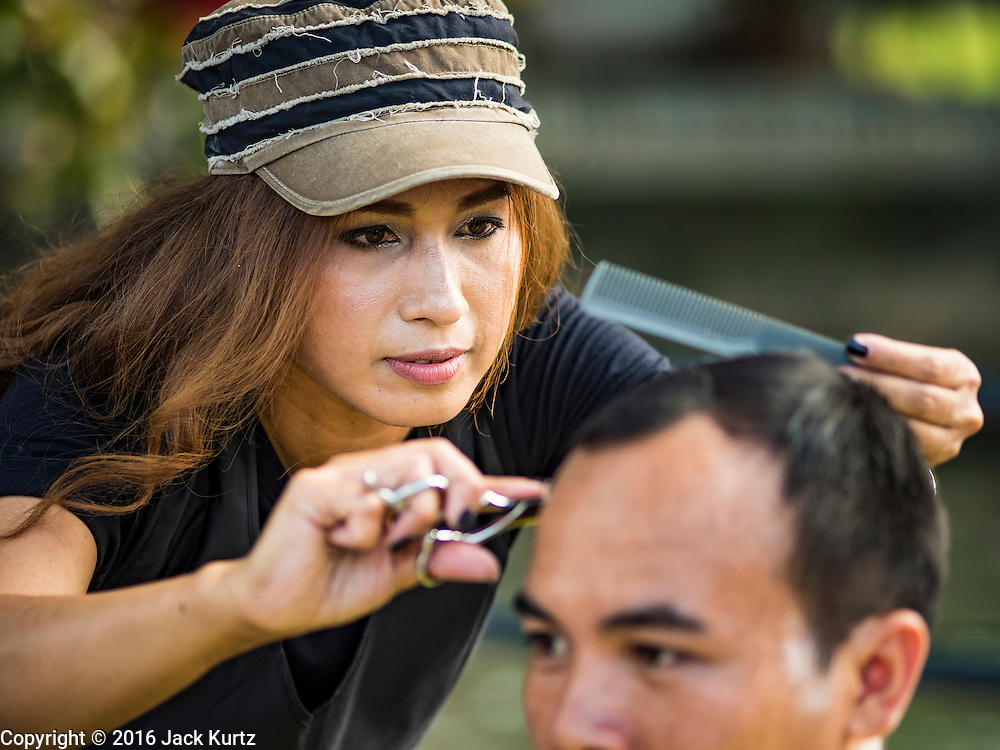 05 NOVEMBER 2016 - BANGKOK, THAILAND: Barbers on Damrong Rak Street, near the Grand Palace, give free haircuts to people going to the palace to mourn the King. Thais are honoring their late King, Bhumibol Adulyadej, also known as Rama IX in various ways. Many barbers are offering mourners free haircuts on the streets near the Grand Palace, where the King is lying in state and communities around the palace are offering free meals to mourners walking to the palace.     PHOTO BY JACK KURTZ