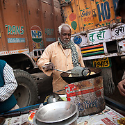 truck drivers having chhole bhatura, a traditional Indian breakfast, at a makeshift restaurant set up at a truck depot outside of Delhi.