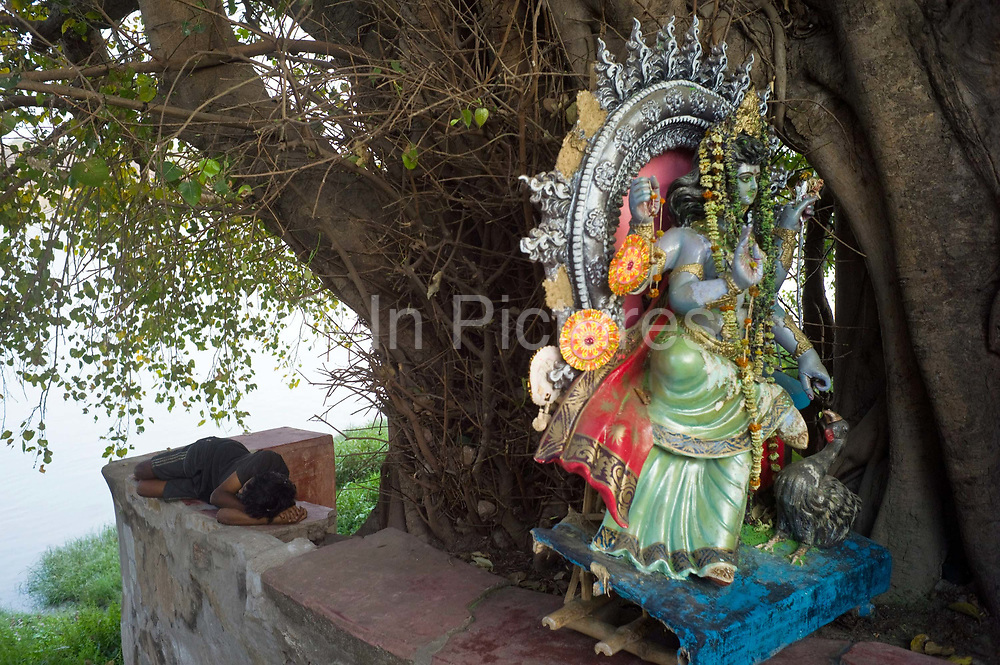 A man sleeps on a shrine to the Goddess Durga on the banks of the Hooghley River, Chandannagar, India