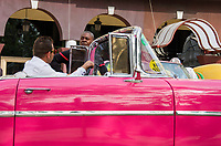 Havana, Cuba - Taxis wait for fares near Hotel Parque Central and Hotel Plaza. Classic American cars from the 1950s, imported before the U.S. embargo, are commonly used as taxis in Havana.