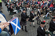 A Scottish saltire being waved by a member of the crowd as a traditional Scottish pipe band marches past during Pipefest Stirling, an event staged at Stirling Castle to coincide with the 700th anniversary of the Battle of Bannockburn. The event was attended by 1600 pipers, Highland dancers and other musicians and formed a procession through the city's streets. The Battle of Bannockburn took place in 1314 and resulted in the defeat of Edward II's English army by the Scots under Bruce.