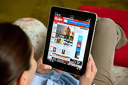 Woman using iPad tablet computer at home to read The Sun tabloid UK newspaper