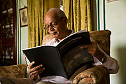 """Nobleman Nahar Singhji, also known as Rao Saheb  sits in his living room reviewing a book he has written at his lake side home on the grounds of the Deogarh Mahal Palace, now a heritage hotel.  This architectural jewel was, prior to it becoming so in 1996, a fortress - palace, dating back 340 years. It belonged to the Mewar aristocracy, their magnificent fort a fitting stronghold for one of its sixteen """"umraos"""" - the most senior feudal barons attending on the Maharana of Udaipur, Rajasthan,"""