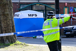 © Licensed to London News Pictures. 23/02/2021. London, UK. Police officer guards a police tent on West Green Road in Tottenham, north London after a fatal stabbing of a man, believed aged in his 20s. Police were called at approximately 16:00hrs on Monday, 22 February to reports of a man, been stabbed. Officers and London Ambulance Service attended but despite the efforts of the emergency services, he was pronounced dead at the scene. Anas Mezenner, 17, was murder not far from the crime scene on 19 January. Photo credit: Dinendra Haria/LNP