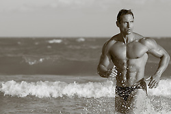 muscular man running through the ocean waves in Florida