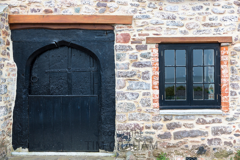 Typical traditional wooden cottage door and casement window on old stone building at Porlock in Somerset, United Kingdom