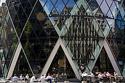 Afternoon drinkers enjoy warm summer sunshine beneath the architecture of the Swiss Re building aka The Gherkin, on 17th Juy 2017, in the City of London, England.