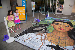 North America, United States, Washington, Bellevue, two girls by chalk art portrait of Freda Kahlo in front of Bellevue Arts Museum during annual ArtsFair