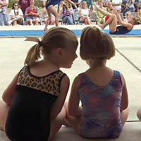 Mackenzie Mardis, left leans over and whispers to her tumbling friend Chelsey Barrow while tumblers tumble in the background, during the Brazoria County Baby & Tot Festival, 10/19/02.  Mardis and Barrow were part of the Mighty Mights 3/4/5 years old tumbling group that performed at the festival