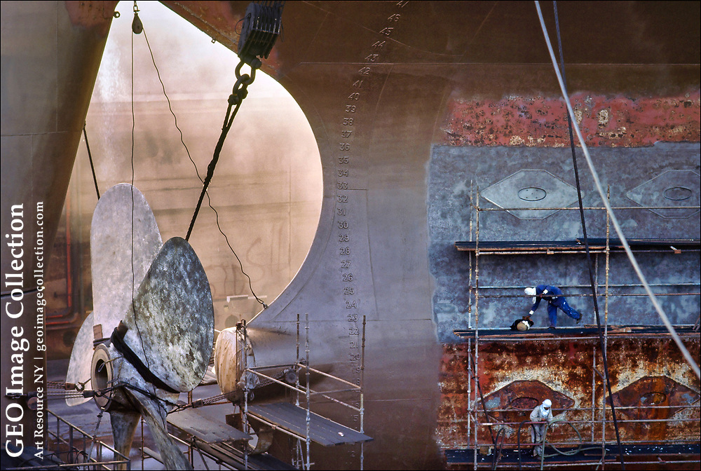 Workmen (lower right) are dwarfed by the size and scale of a mammoth super-tanker receiving a new paint job at the Arab Shipbuilding and Repair Yard at Al Hidd in Bahrain on the Persian Gulf.