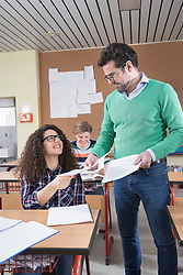 Teacher handing papers to students in classroom, Bavaria, Germany