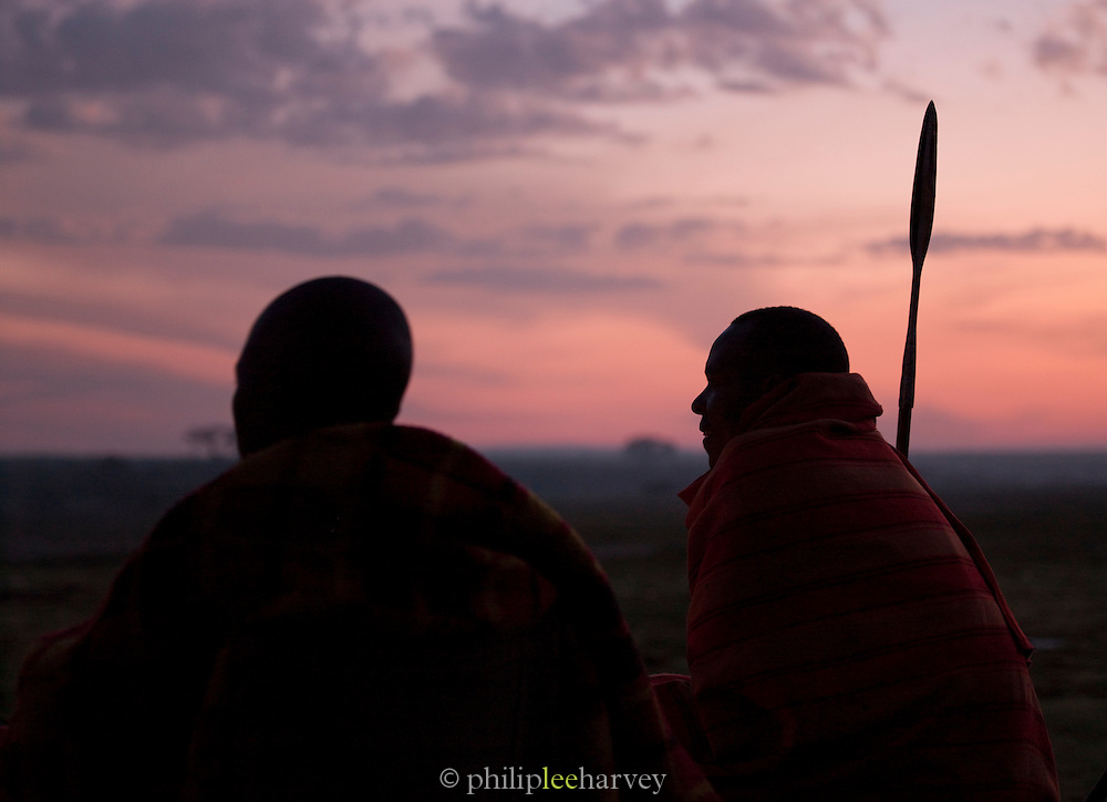 Maasai tribesmen at sunset looking over plains, Maasai Mara National Reserve, Kenya