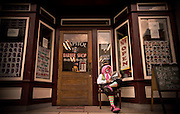 A clown in full costume sits and reads the newspaper in front of a downtown barber shop.