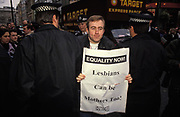 "A Gay rights protester is arrested by Met Police officers while still carrying an 'Equality Now!"" sheet from the campaigning group 'Outrage!', on 6th February 1992, in London, England."