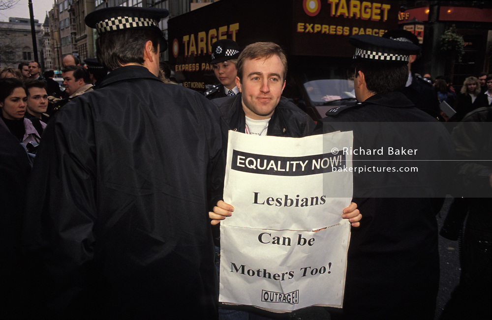 """A Gay rights protester is arrested by Met Police officers while still carrying an 'Equality Now!"""" sheet from the campaigning group 'Outrage!', on 6th February 1992, in London, England."""