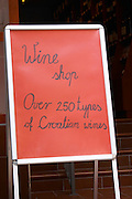 A red sign post with black writing advertising a wine shop with the text 'Wine shop, over 250 types of Croatian wines' on the Luza Lodge Loggia Square Dubrovnik, old city. Dalmatian Coast, Croatia, Europe.