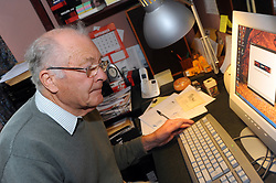 An elderly man uses his computer at home. Model released