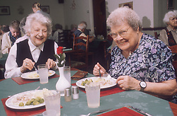 Two elderly women eating meal in residential home,