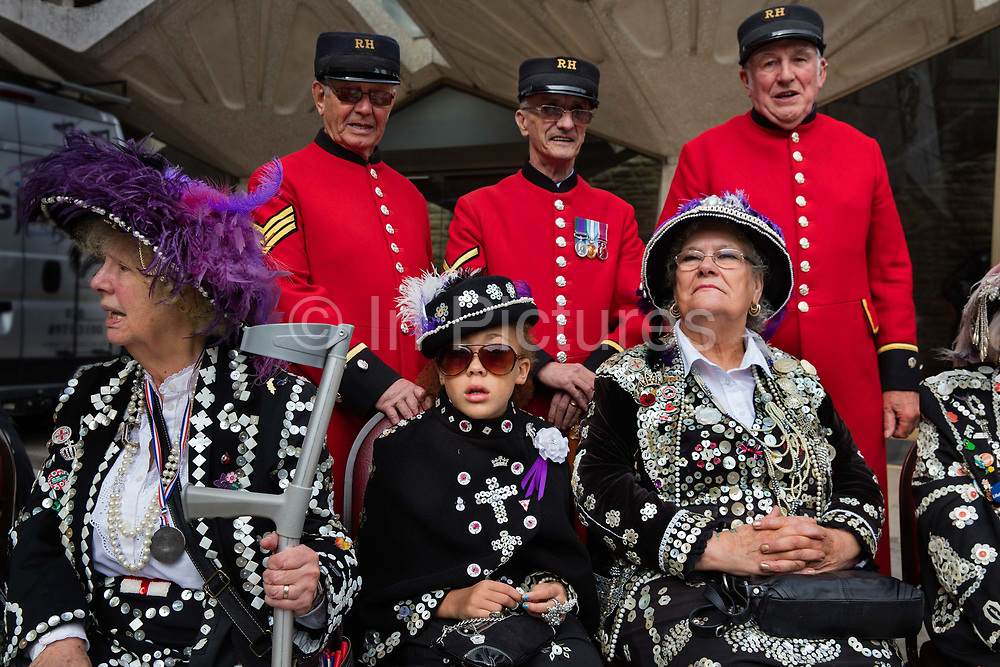 Grandmother & Granddaughter at the Pearly Kings and Queens Harvest Festival celebrations at Guildhall Yard. The annual event features early English entertainment including maypole dancing, Morris dancers and a marching band. The Chelsea pensioners & all the mayors of London take part in this traditional London event.<br /> The London tradition of the Pearly Kings and Queens began in 1875, by Henry Croft. Inspired by the local Costermongers, a close-knit group of market traders who looked after one another and were recognisable by buttons sewed onto their garments, Henry went out on the streets to collect money for charity, wearing a suit covered in pearl buttons to attract attention. When demand for his help became too much, Henry asked the Costermongers for assistance, many of whom became the first Pearly Families. Today, around 30 Pearly Families continue the tradition to raise money for various charities.