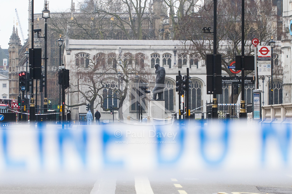 Westminster, London, March 23rd 2017. Forensic officers conduct a fingertip search on Parliament Square as investigations continue following Tuesday's terrorist attack on Westminster Bridge and in the grounds of Parliament, in which four people and their attacker were killed with over 40 injured.