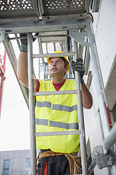 Construction worker at building site climbing up a ladder, Munich, Bavaria, Germany