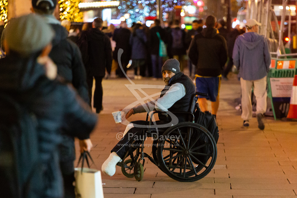 A man in a wheelchair begs on Oxford Street. Homeless Britons are coming under increasing pressure as a surge of Roma beggars from Romania arrive on the streets of London to take advantage of the generosity of Christmas shoppers. London, December 04 2018.