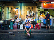 17 JANUARY 2016 - BANGKOK, THAILAND: A food stand vendor checks his smart phone while he waits for customers on Sukhumvit Soi 38, one of the most famous street food areas in Bangkok. The food carts and small restaurants along the street have been popular with tourists and Thais alike for more than 40 years. The family that owns the land along the soi recently decided to sell to a condominium developer and not renew the restaurant owners' leases. More than 40 restaurants and food carts will have to close. Most of the restaurants on the street closed during the summer of 2015. The remaining restaurants are supposed to close by the end of this week.         PHOTO BY JACK KURTZ