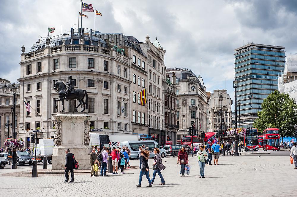 London, UK - August 11, 2014: People enjoy the sunny weather in Trafalgar Square in London