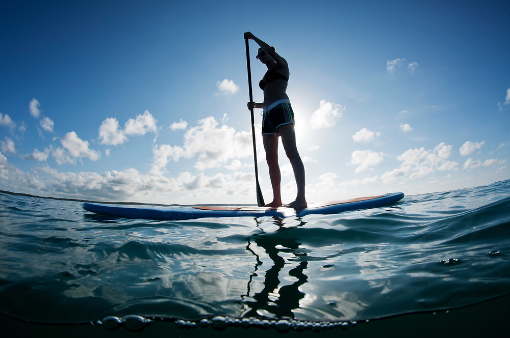 A stand up paddle board or SUP board rider enjoys a beautiful evening in The Bahamas.