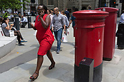 A businesswoman walk and talks on Leadenhall in the City of London, the capital's financial district (aka the Square Mile), on 10th July 2019, in London England.