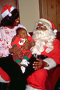 Black Mom and Santa (Dad) age 25 with their baby a Christmas benefit.  Minneapolis Minnesota USA