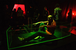 © Licensed to London News Pictures. 10/08/2017. London, UK. A visitor lies in a lit neon green coffin and takes a selfie photo controlling a camera in the ceiling above them.  The artwork titled Beauty and Dead by artists Jim Townsend and Oli Cole is part of the Be Seen Dead exhibition by Made By Blah, exploring how death impacts our own identity, mortality and out complex attitudes towards it. Photo credit: Ray Tang/LNP