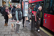 Street scene on Oxford Street, London, UK. People josstle. walk and wait for public transport buses at the many bus stops on this main shopping district.