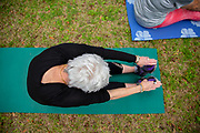 Senior woman stretching on a yoga mat outside