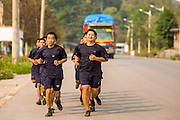 14 MARCH 2013 - BOTEN, LAOS:  Lao police officers jog through the Boten Special Economic Zone in Boten, Laos. The SEZ is dominated by Chinese businesses. PHOTO BY JACK KURTZ